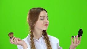 Het schoolmeisje poederde haar neus met een borstel Het groene scherm stock footage