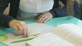 Het schoolmeisje schrijft in haar voorbeeldenboek bij de les stock footage