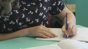 Het schoolmeisje schrijft in haar voorbeeldenboek bij de les stock video
