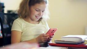 Het schoolmeisje sluit het boek en neemt gaily haar roze mobiele telefoon Mededeling in sociale netwerken Problemen van stock footage