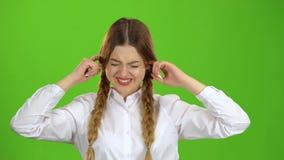 Het schoolmeisje sluit zijn oren van het lawaai Het groene scherm stock footage