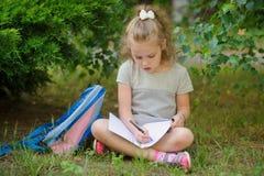 Het schoolmeisje van basisschool zit hebben gekruistd benen onder een boom en doet thuiswerk Stock Afbeeldingen