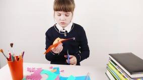 Het schoolmeisje verwijdert met schaar van document stock videobeelden