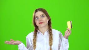 Het schoolmeisje in witte blouse met een creditcard is droevig Het groene scherm stock videobeelden