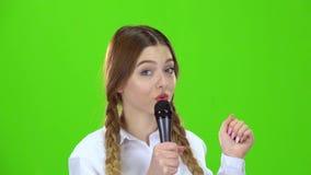 Het schoolmeisje zingt in de microfoon en glimlacht Het groene scherm stock videobeelden