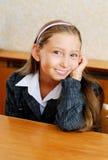 Het schoolmeisje zit bij een schoolbank Royalty-vrije Stock Foto's