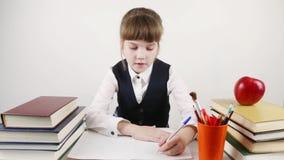 Het schoolmeisje zit bij lijst en schrijft dichtbij boeken stock videobeelden