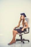 Het schoolmeisje zit op stoel, denkend over toekomst stock foto