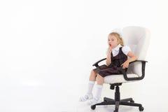 Het schoolmeisje zit op stoel en vraagt stil te zijn royalty-vrije stock foto's