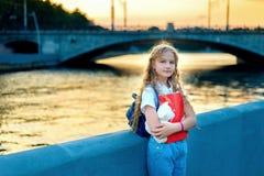 Het schoolmeisjeblonde met blauwe ogen bevindt zich dichtbij de rivier in de stad bij zonsondergang stock afbeelding