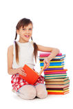 Het schoolmeisjezitting van Smiley dichtbij boeken Stock Foto's