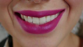 Het schoonheidsbrunette neemt een rood lint van haar lippen stock videobeelden