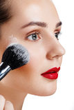 Het schoonheidsmeisje met borstel beëindigt make-up van toepassing is highlighter Helder M Stock Fotografie