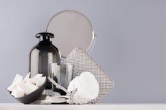 Het schoonheidsmiddel en maakt omhoog tot toebehoren en huisdecoratie zwarte glasvaas, zilveren spiegel, kommen op zachte witte h stock afbeeldingen