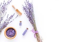 Het schoonheidsmiddel met lavendelkruiden wordt geplaatst en het overzeese zout in fles op witte lijstvlakte als achtergrond legg stock afbeelding