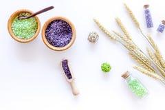 Het schoonheidsmiddel met tarwekruiden en overzees zout in fles op witte lijstvlakte wordt geplaatst die als achtergrond lag royalty-vrije stock fotografie