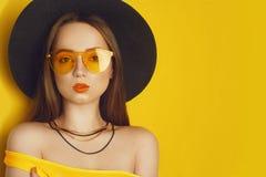 Het schoonheidsmodel met oranje beroeps kijkt toebehoren Maniervrouw met lang, recht haar De tendens maakt omhoog Oranje Achtergr royalty-vrije stock foto
