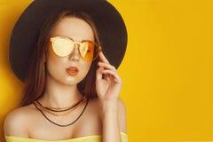 Het schoonheidsmodel met oranje beroeps kijkt toebehoren Maniervrouw met lang, recht haar De tendens maakt omhoog Oranje Achtergr royalty-vrije stock afbeelding