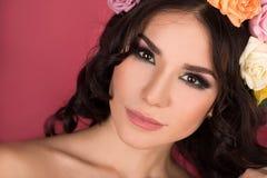Het schoonheidsportret van een vrouw met een kroon van bloemen op haar leidt een rode achtergrond Stock Afbeeldingen