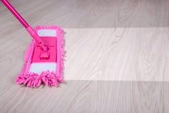 Het schoonmaken concept - sluit omhoog van zwabber schoonmakend houten vloer Royalty-vrije Stock Afbeeldingen