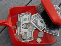 Het schoonmaken en het vegen op geld met een blik en een bezem stock foto