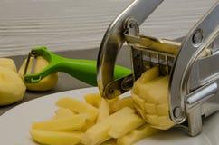 Het schoonmaken en het snijden met brusks op de aardappelsnijder stock afbeeldingen