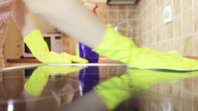 Het schoonmaken van cooktop kokend paneel in keuken met vette vlekkenmiddelennevel en een stofdoek door een vrouw in gele rubberh stock video