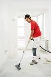 Het schoonmaken van de arbeider vloer thuis vernieuwing stock foto's