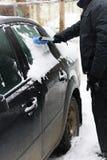 Het schoonmaken van de auto van sneeuw stock afbeelding