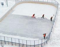 Het schoonmaken van de ijsbaan van de sneeuw in de werf van het huis Stock Foto's
