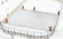Het schoonmaken van de ijsbaan van de sneeuw in de werf van het huis Royalty-vrije Stock Afbeeldingen