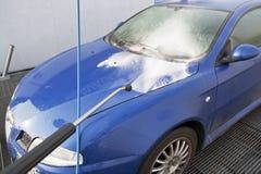 Het schoonmaken van een auto met water en zeep in carwash Stock Afbeeldingen