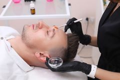 Het schoonmaken van het gezicht van een mens in een schoonheidssalon stock afbeeldingen