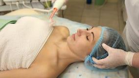 Het schoonmaken van het gezicht van een vrouw met behulp van nieuwe technologieën stock video