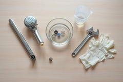 Het schoonmaken van limescale op de filter van de kraan die thuis een het schoonmaken oplossing gebruiken Azijn ets limescale royalty-vrije stock foto