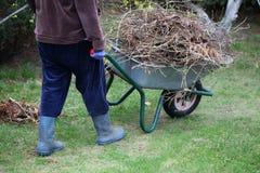 Het schoonmaken van tuin die kruiwagen met behulp van Royalty-vrije Stock Foto