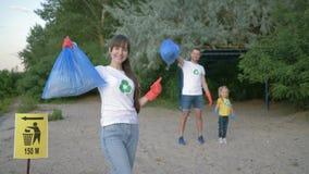 Het schoonmakende strand, portret van jongelui meldt zich moeder in rubberhandschoenen met vuilniszak dichtbij wijzerteken op aan stock video