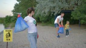 Het schoonmakende strand, portret van jongelui meldt zich moeder in rubberhandschoenen met vuilniszak dichtbij wijzerteken op aan stock videobeelden