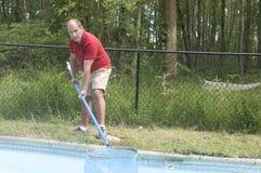 Het schoonmakende zwembad van de huiseigenaar stock fotografie