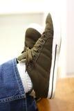 Het schoppen terug met benen die bij enkels worden gekruist Stock Fotografie