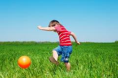 Het schoppen van de jongen bal stock foto's