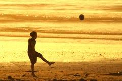 Het schoppen van de jongen bal op strand Royalty-vrije Stock Afbeeldingen