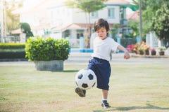 Het schoppen van de jongen voetbal stock afbeeldingen
