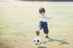 Het schoppen van de jongen voetbal stock foto