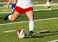 Het schoppen van een voetbalbal tijdens een spel royalty-vrije stock foto's