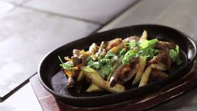 Het schot van fryed groenten met vlees in hete pan op houten tribune stock videobeelden