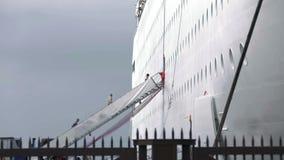 Het schot van mensen die de treden op witte kruiser stijgen in te schepen maakte achter omheining stock footage