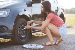 Het schot van mooie jonge ervaren vrouwelijke bestuurder probeert om autowiel te veranderen, gebruikt noodzakelijke instrumenten  stock foto