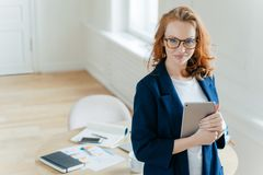 Het schot van mooie rode haired jonge vrouw controleert bericht op aanraking stootkussen, gelukkig om te ontvangen inkomen berich royalty-vrije stock foto's