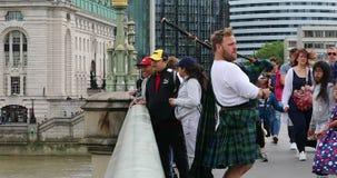 Het Schotse Bagpiper Spelen op een Brug in Londen stock videobeelden